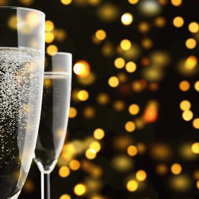 Three Champagne glasses with sparkling lights in background