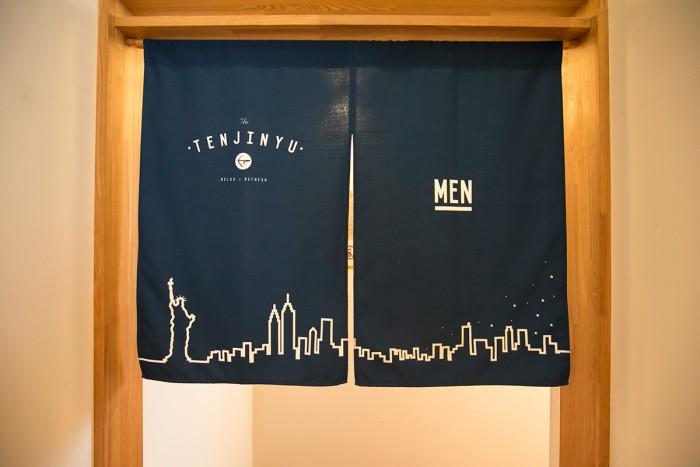 """ニューヨークのビル群が描かれた、粋なオリジナル暖簾。""""入浴""""とかけて・・・。"""