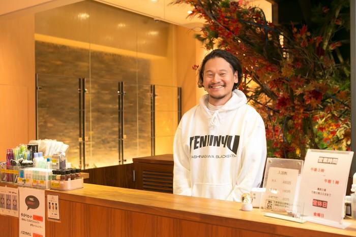 オリジナルパーカーを着た岡村周明さん。