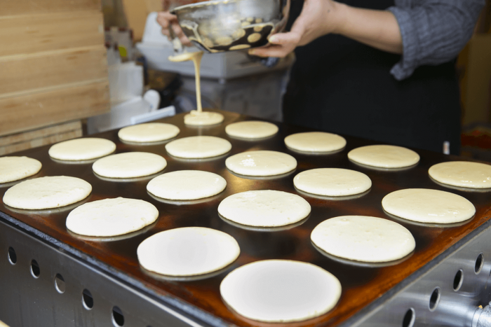 Batter is poured onto the griddle, evenly spaced and all the same size.